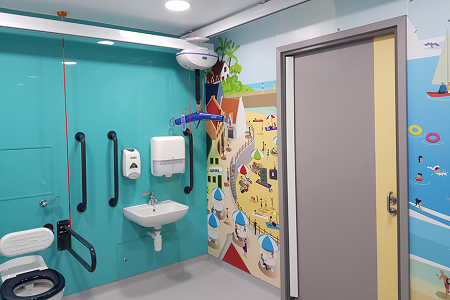 Children supported by beach-themed inclusive washroom